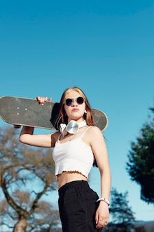 A young caucasian woman with sunglasses and headphones holding a skateboard over her shoulder. in the background, blue sky and trees