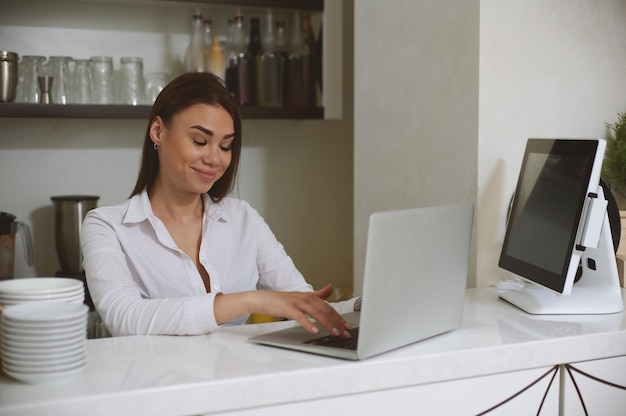 Young caucasian woman with a surprised face communicates using laptop