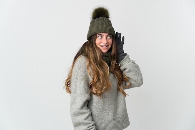 겨울 모자와 젊은 백인 여자는 귀에 손을 넣어 뭔가를 듣고 흰색 배경에 고립