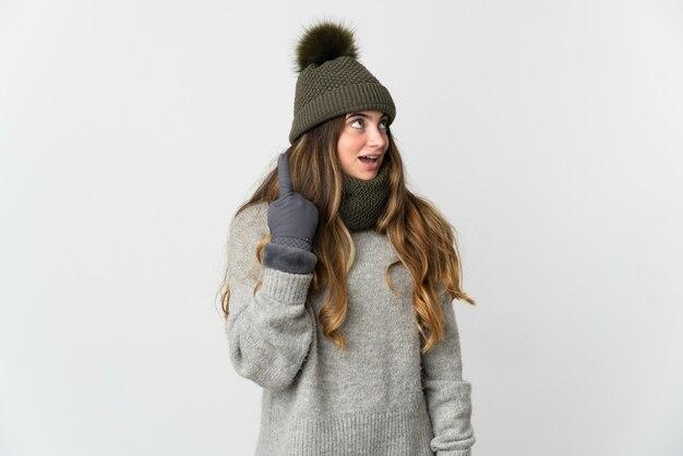 손가락을 가리키는 아이디어를 생각하는 흰색 배경에 고립 된 겨울 모자와 젊은 백인 여자