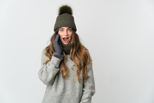 놀람과 충격 된 표정으로 흰색 배경에 고립 된 겨울 모자와 젊은 백인 여자
