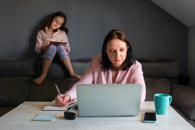 彼女のラップトップで自宅で働く若い白人女性。彼女の娘は彼女のタブレットで彼女の漫画を見ているの隣に座っています