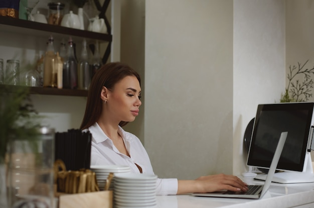 A young caucasian woman works in a laptop behind a bar