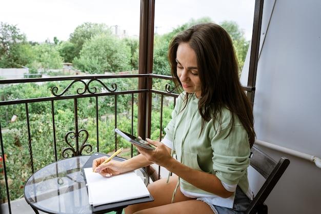 젊은 백인 여자는 여름 발코니에 그녀의 손에 전화와 캐주얼 옷에 펜으로 노트북에 씁니다