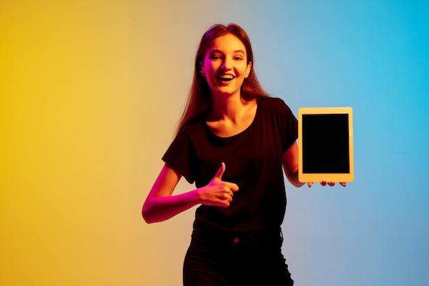 네온 불빛에 그라데이션 blueyellow 스튜디오 배경에 젊은 백인 여자 초상화