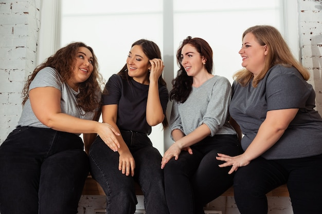 Young caucasian women in casual clothes having fun together. friends sitting near by window and laughting, spending time together. bodypositive, nutrition, feminism, loving themself, beauty concept.
