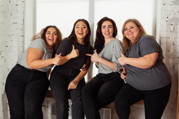 Giovani donne caucasiche in abiti casual divertendosi insieme. amici seduti vicino alla finestra e ridono, trascorrono del tempo insieme. bodypositive, nutrizione, femminismo, amare se stessi, concetto di bellezza.