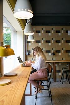 ノートパソコンで作業し、コーヒーを飲む若い白人女性