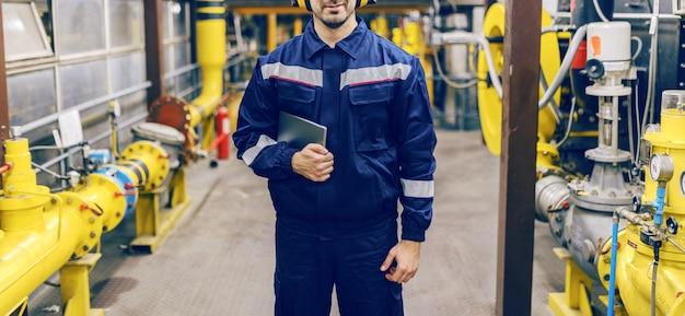 Молодой кавказский работник в защитном костюме держа таблетку и стоя в заводе жары.