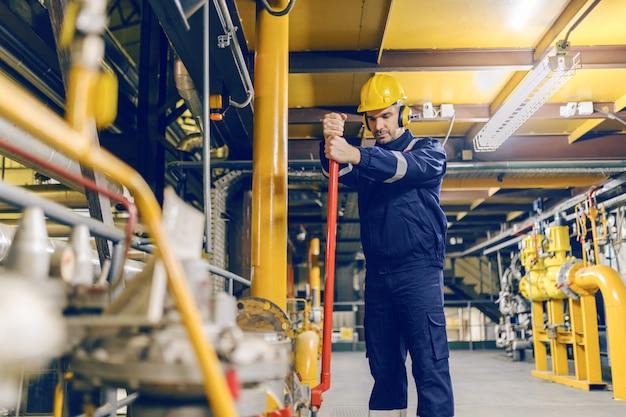 Молодой кавказский работник в защитном костюме затягивая клапан пока стоящ в отопительной установке.