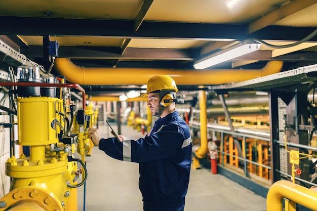 Молодой кавказский работник в защитном костюме используя таблетку пока проверяющ машины в заводе отопления.