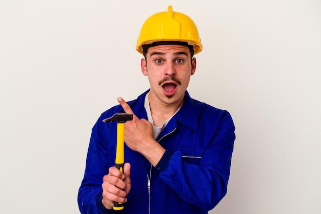 Молодой кавказский рабочий мужчина держит молоток на белом фоне, указывая в сторону