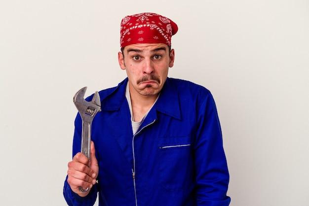 Молодой кавказский рабочий человек, держащий гаечный ключ на белом фоне, пожимает плечами и смущает открытые глаза.
