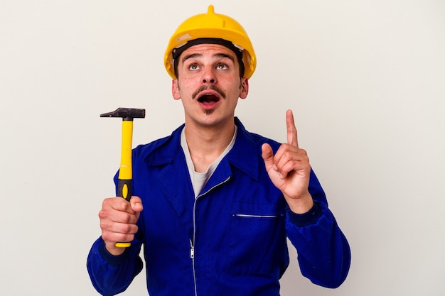 Young caucasian worker man holding a hammer isolated on white background pointing upside with opened mouth.