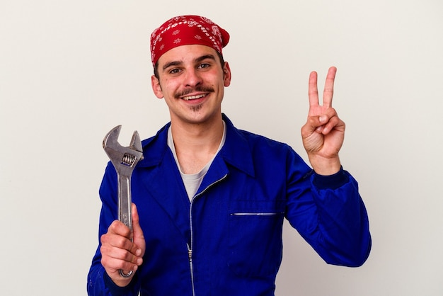 Young caucasian worker man holding a spanner isolated on white background joyful and carefree showing a peace symbol with fingers.