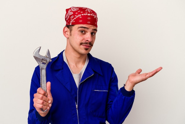 Young caucasian worker man holding a spanner isolated on white background showing a copy space on a palm and holding another hand on waist.