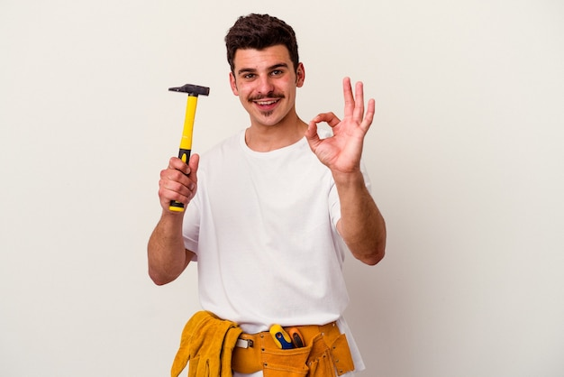 陽気で自信を持って ok のジェスチャーを示す白い背景で隔離のツールを持つ若い白人労働者の男