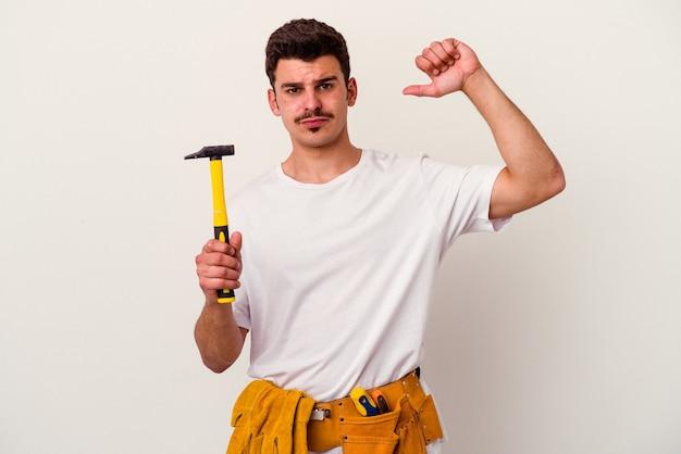 Молодой кавказский рабочий человек с инструментами, изолированными на белом фоне, чувствует себя гордым и уверенным в себе, примером для подражания.