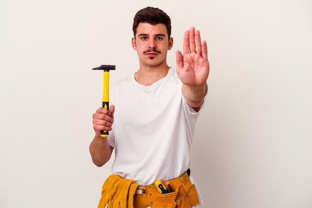 白い背景に孤立したツールを持つ若い白人労働者の男は、一時停止の標識を示す差し出された手で立って、あなたを防ぎます。