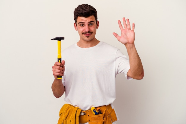 Young caucasian worker man with tools isolated on white background smiling cheerful showing number five with fingers.