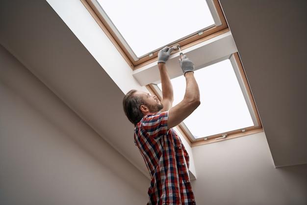 Young caucasian worker screwing skylight window handle