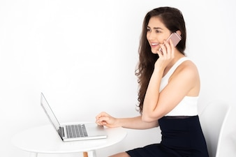 Young Caucasian working business woman talking on phone and working on laptop