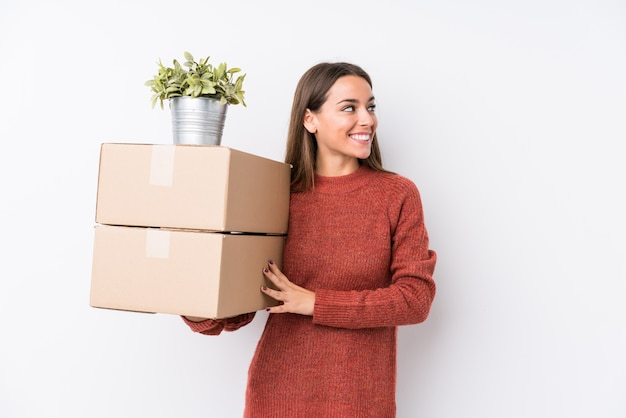Молодая кавказская женщина, держащая коробки смотрит в сторону, улыбаясь, веселая и приятная.