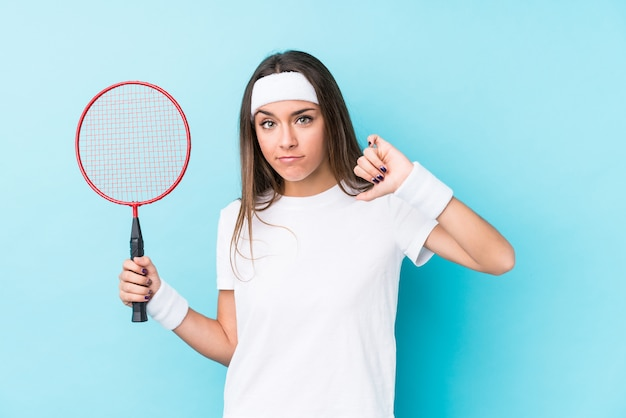 Young caucasic woman playing badminton isolated showing a dislike gesture, thumbs down. disagreement concept.
