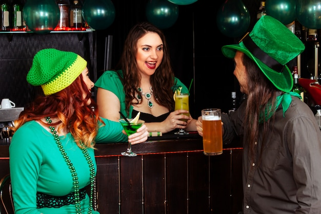 Young celebrate patrick day fun bar carnival headgear girl man beer cocktail green clothes hat smile beautiful leprechaun