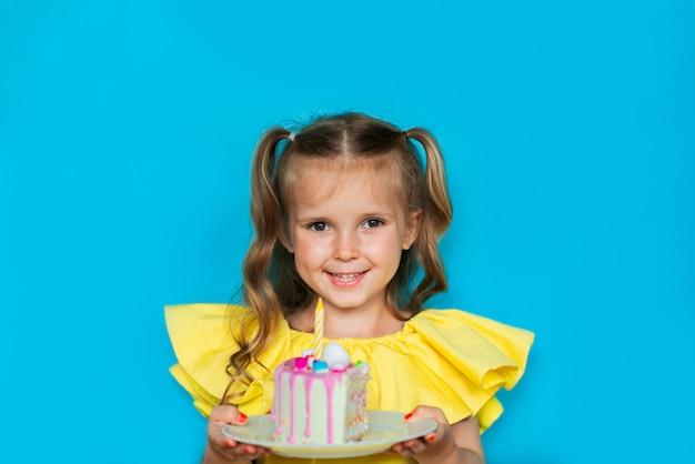 파란색 배경에 케이크 한 조각을 들고 젊은 축 하 소녀. 공간 복사