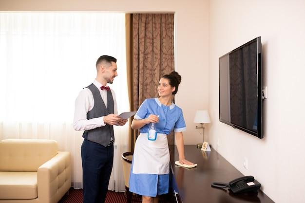 직장에서 호텔 객실 중 하나에서 상호 작용하는 터치 패드가있는 포터와 세제와 먼지 떨이가있는 젊은 챔버 메이드
