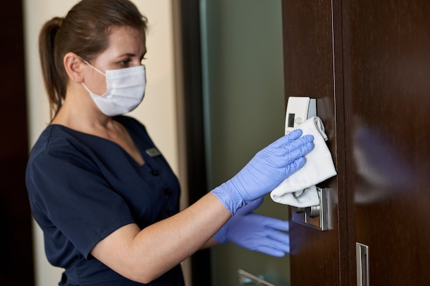 Молодая горничная дезинфицирует поверхности в гостиничном номере с тряпкой