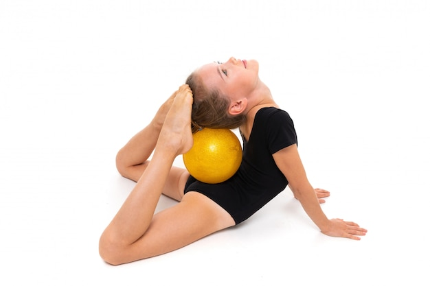 Young champion girl in a black swimsuit is stretching with the ball on a white wall