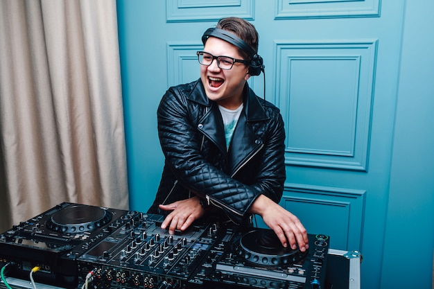 Young charismatic dj in glasses and leather jacket. cool dj at work.