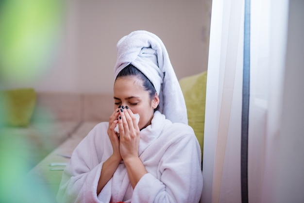 Young charming beautiful woman in a robe and with a towel on her head is wiping her nose after sneezing while sitting on the floor leaning against the sofa.