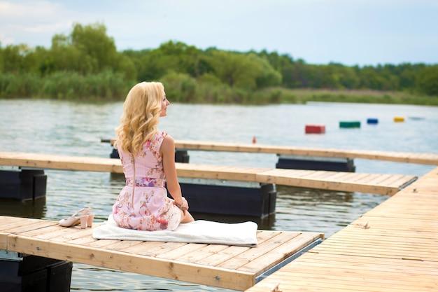 Молодая очаровательная белокурая девушка сидит одна на деревянном пирсе и смотрит на реку