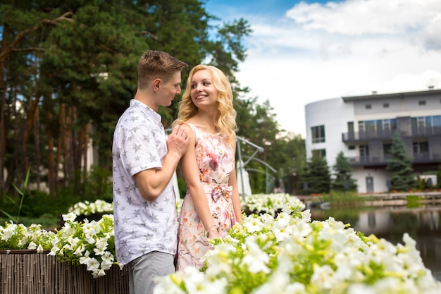 Young charming blonde girl is flirting and with a guy in the garden. lovestory of a couple in love
