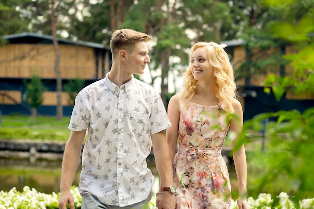 Young charming blonde girl is flirting and with a guy in the garden. lovestory of a couple in love.