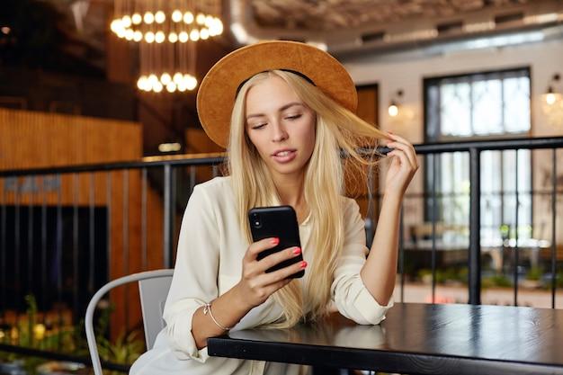 Молодая очаровательная блондинка с длинными волосами держит мобильный телефон в руке и смотрит на экран со спокойным лицом, в коричневой шляпе и белой рубашке