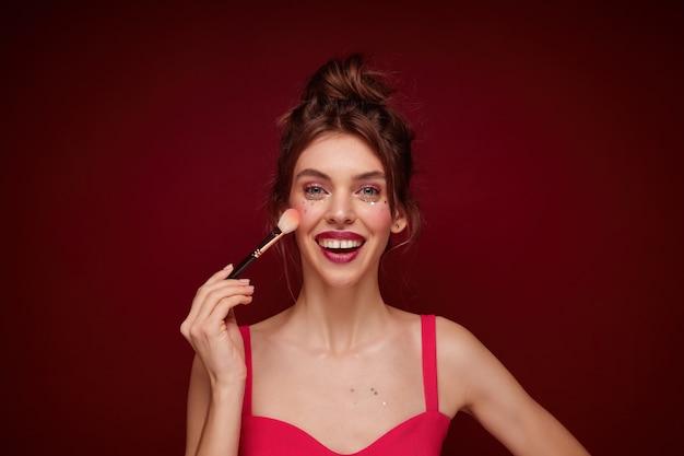 お祝いの化粧を身に着けて、彼女の手でブラシで立っているストラップとピンクのトップの若い魅力的な茶色の髪の女性