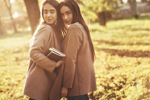 Young charming brunette twin girls standing very close turned to each other in casual coat , touching heads at autumn sunny park on blurry background. one of them is holding books with her eyes closed