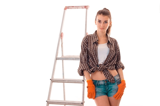 Young charming builder woman in uniform with ladder makes renovation isolated on white wall