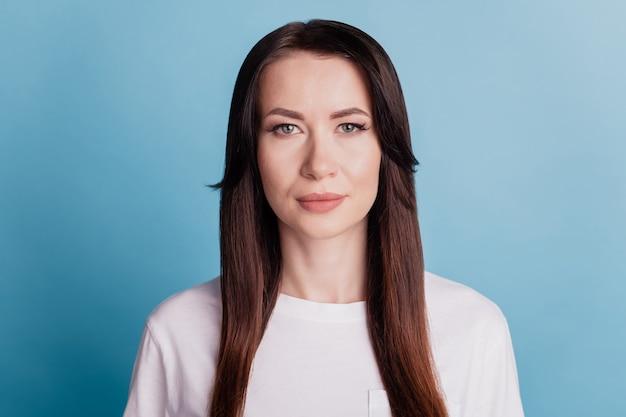 Молодая очаровательная кавказская женщина с длинными каштановыми волосами и серьезным выражением лица изолирована на синем фоне