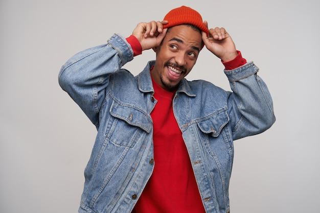 Giovane affascinante ragazzo barbuto dalla pelle scura che guarda felicemente da parte con un ampio sorriso mentre tiene le mani sul suo berretto, isolato su un muro bianco in abbigliamento casual