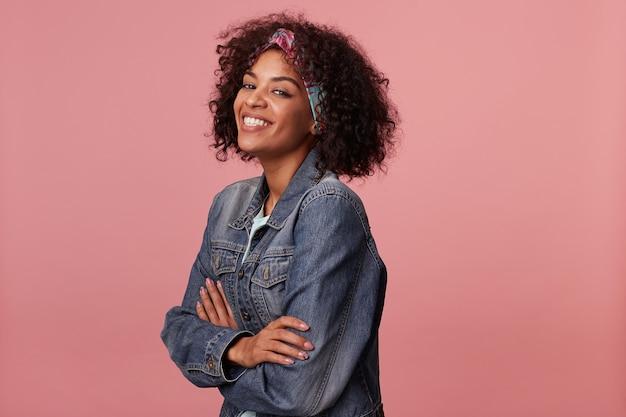 Молодая очаровательная темнокожая женщина в яркой повязке на голову с короткими вьющимися волосами, счастливо улыбается, позируя со сложенными руками