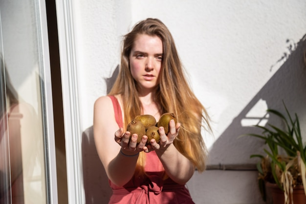 Young charming female in casual summer dress sitting on balcony and offering tropical fresh juicy kiwis