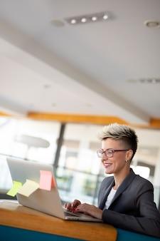 座っている間距離の仕事のためにラップトップコンピューターを使用して若い魅力的な女性のフリーランサー