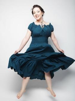 Молодая очаровательная женщина в синем платье прыгает через серый фон