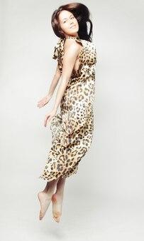 Молодая очаровательная женщина в шифоновом платье прыгает через серый фон