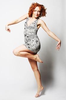 Молодая очаровательная женщина в платье прыгает на белом фоне